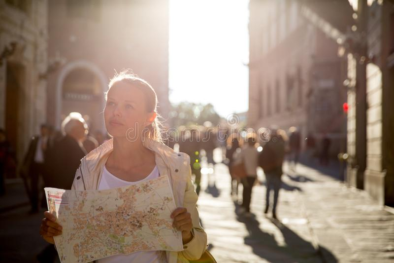 Gorgeous female tourist with a map discovering a foreign city s. Hallow DOF; color toned image backlit by warm evening sunshine royalty free stock photos