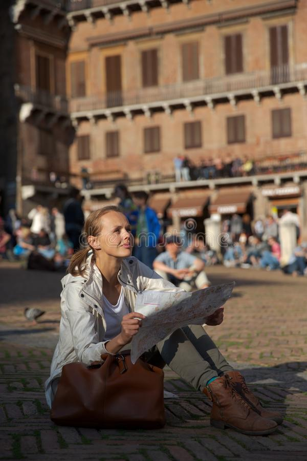 Pretty female tourist with a map discovering a foreign city. Shallow DOF; color toned image stock photos