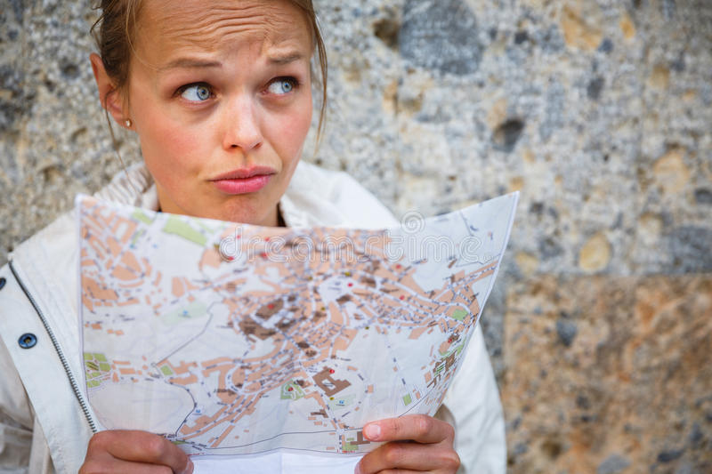 Gorgeous female tourist with a map discovering a foreign city. (shallow DOF; color toned image royalty free stock photos