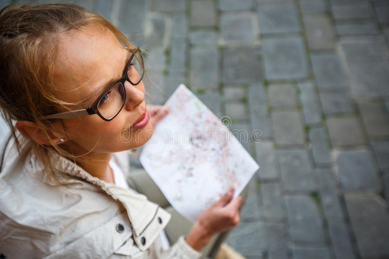 Gorgeous female tourist with a map discovering a foreign city. (shallow DOF; color toned image royalty free stock photography