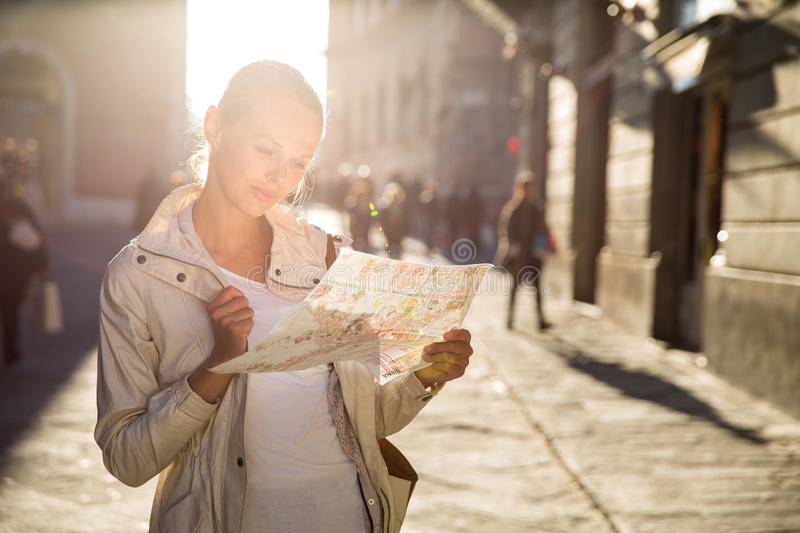 Gorgeous female tourist with a map discovering a foreign city. (shallow DOF; color toned image stock image