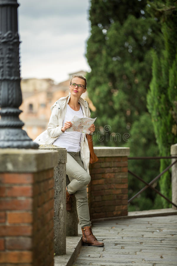 Gorgeous female tourist with a map discovering a foreign city. Shallow DOF; color toned image stock photography
