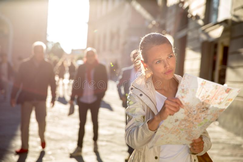 Pretty female tourist with a map discovering a foreign city. Shallow DOF; color toned image stock photo