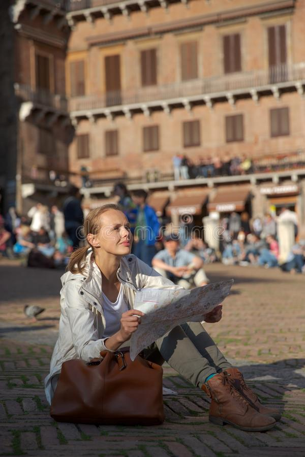 Gorgeous female tourist with a map discovering a foreign city. Shallow DOF; color toned image royalty free stock photography