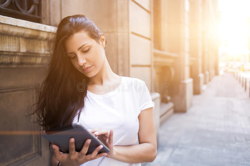 Gorgeous female tourist using touch pad for navigation in city during vacations abroad royalty free stock images