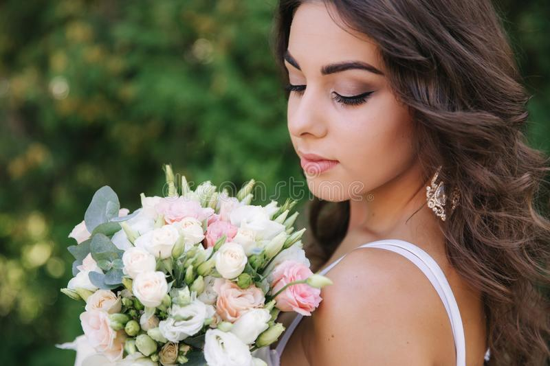 Gorgeous female in white dress slime. Beautiful girl hold a bouquet of flowers in hands royalty free stock image