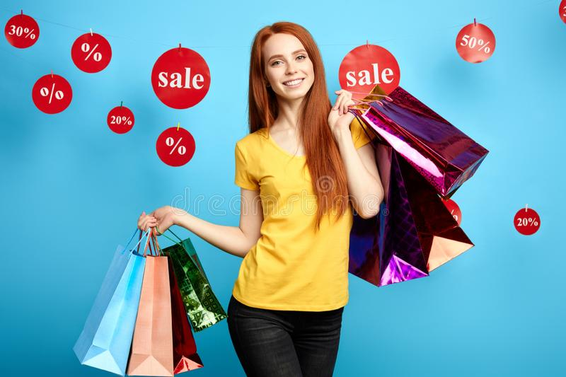 Gorgeous ginger woman is keen on shopping royalty free stock photo