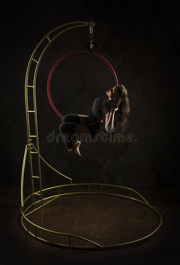 Gorgeous girl, aerial acrobat, in a dark suit performs acrobatic elements on a portable air ring, in the stage light royalty free stock images