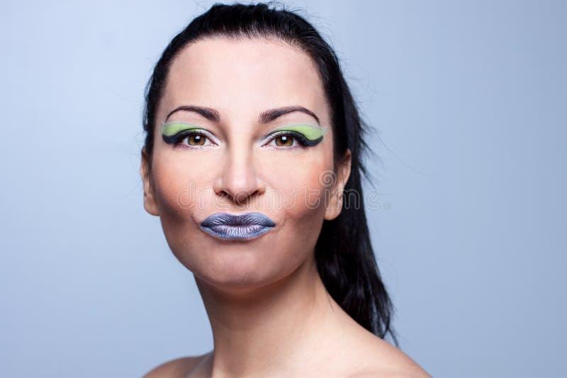Gorgeous girl, brunette kisses kiss gray background bright make-up, joke idea concept stock photos