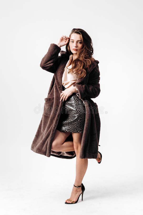 Gorgeous girl dressed in a shirt, leopard skirt and fur coat on high heels poses on the white background in the studio stock images