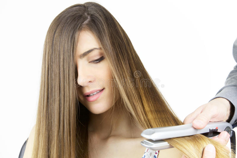Gorgeous girl having long hair straightened isolated closeup. Beautiful woman with very long hair getting hairdo royalty free stock photography