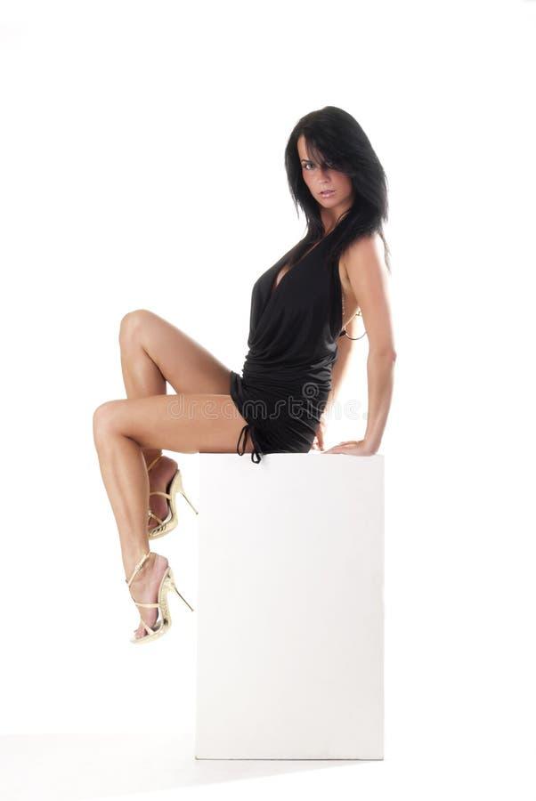 Gorgeous girl sitting on a white cube. In studio stock photo