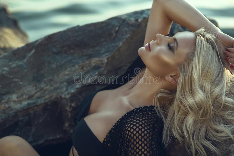 Gorgeous glam tanned blond woman with closed eyes wearing black swimsuit and summer tunic relaxing and bathing in the sun. Close up portrait of gorgeous glam royalty free stock photos