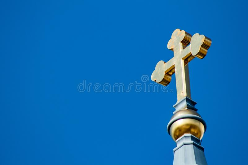 Golden Cross in the Sky. A gorgeous gold cross atop a tall tower royalty free stock images