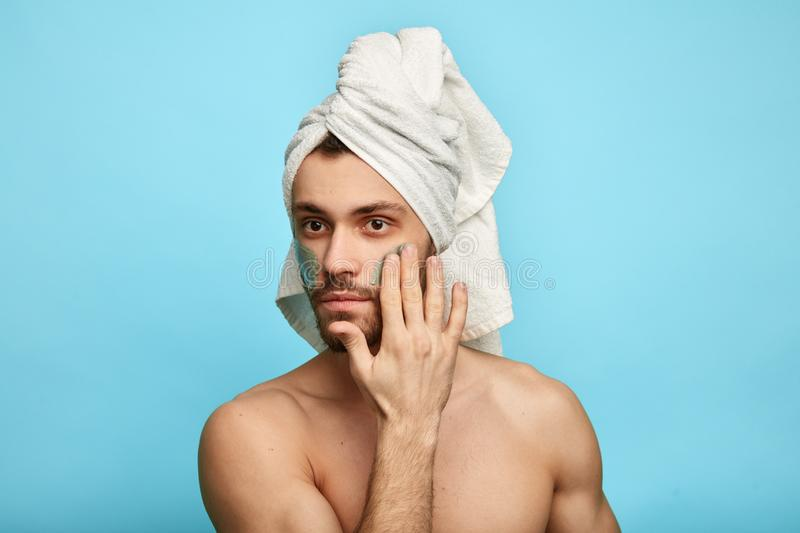 Gorgeous good looking guy with a towel on his head. Massaging his face and putting mask on it, isolated over blue background royalty free stock image