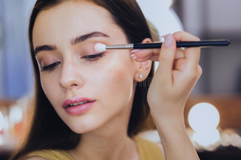 Gorgeous good-looking woman using her eye shadows. Eye shadows. Gorgeous good-looking woman using her eye shadows while holding little face brush in her hand stock photos