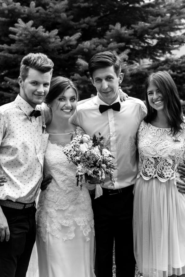 Gorgeous happy bride and groom having photos with friends and fa stock image