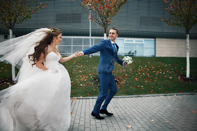 Gorgeous happy brunette bride and elegant groom in blue suit run royalty free stock photo