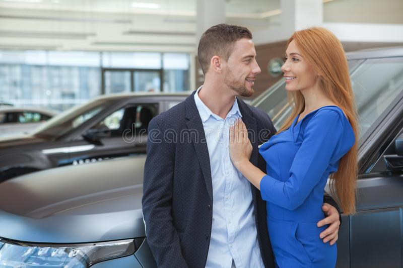 Young classy couple buying luxurious car at the dealership. Gorgeous happy couple hugging at car dealership after buying new automobile, copy space stock images