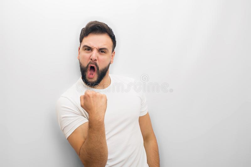 Gorgeous and happy person stands and poses on camera. He holds hand in fist and have joy. He is excited. Isolated on stock photos