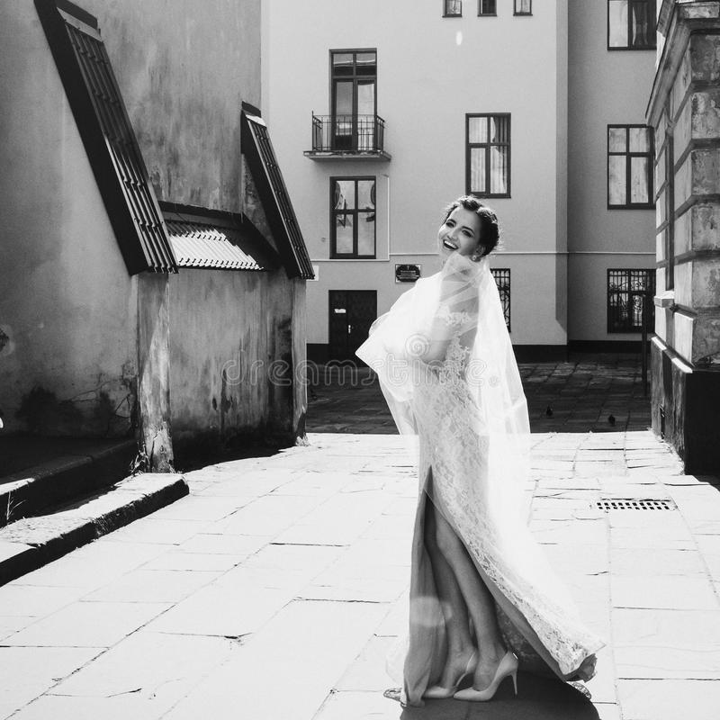 Gorgeous happy smiling brunette bride in vintage white dress posing in the street b&w stock photo