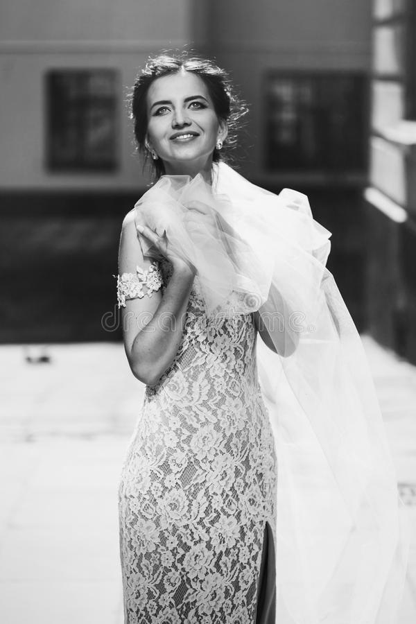 Gorgeous happy smiling brunette bride in vintage white dress posing in the street b&w stock photography