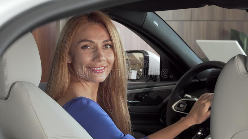 Gorgeous happy woman sitting in expensive new car smiling to the camera stock photo