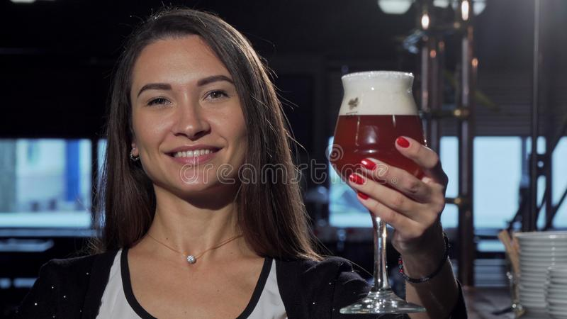 Gorgeous happy woman smiling, holding out her beer to the camera stock photo