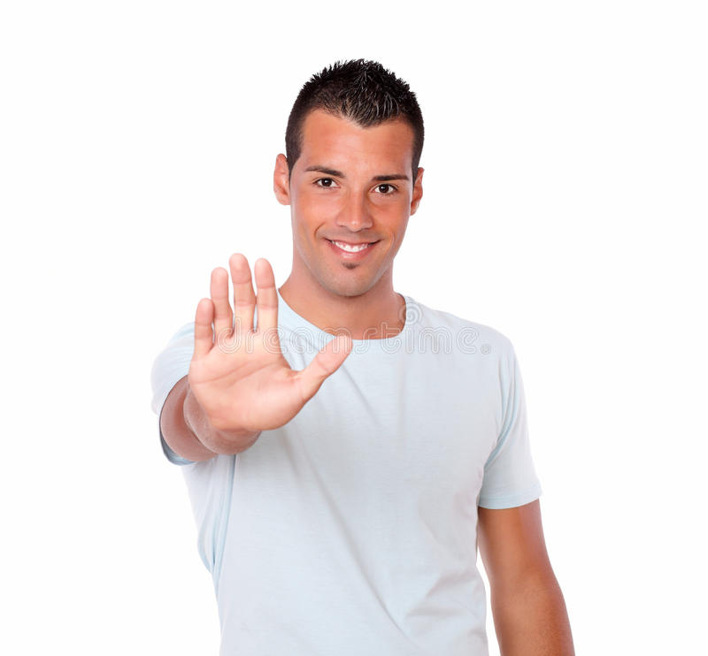 Gorgeous hispanic guy with high gesture. Portrait of a gorgeous hispanic guy on white t-shirt with high gesture standing and looking at you on isolated studio royalty free stock photos