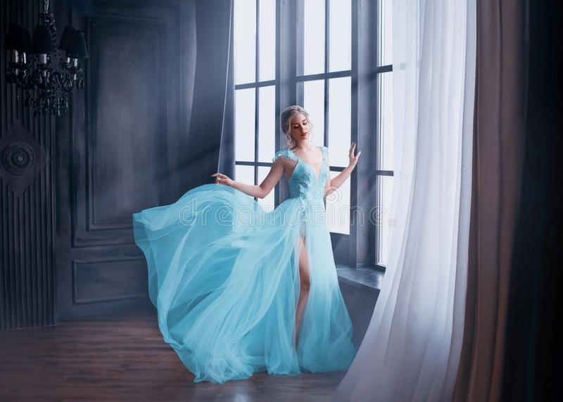 Gorgeous image of graduate in 2019, girl in long blue gentle flying dress with bare leg stands alone, fabulous princess. Elegant lady with blond hair in royalty free stock photos