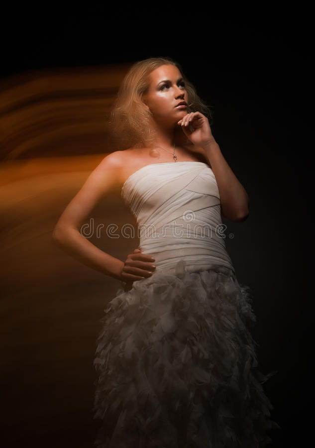 Gorgeous indecisive girl in white dress. On black background royalty free stock photo