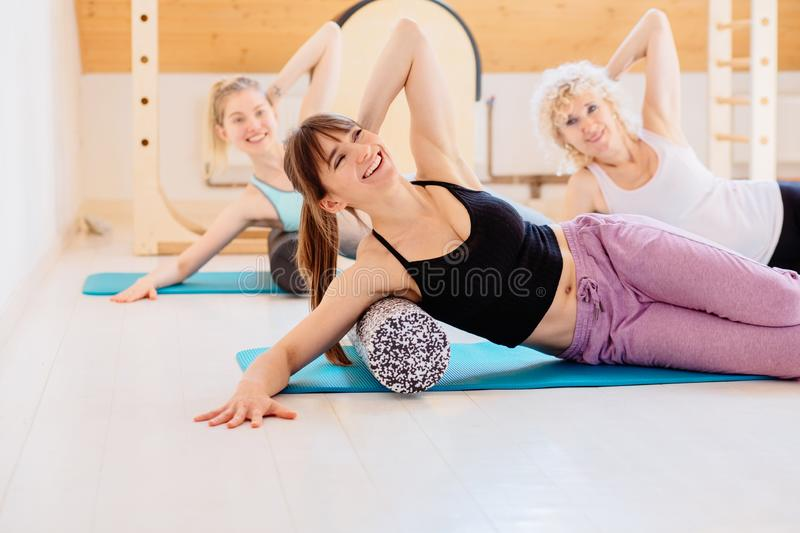 Female instructor with young female and senior woman together using a foam roller for a myofascial release massage at royalty free stock images
