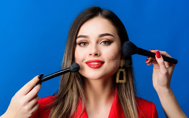 Gorgeous lady make up red lips. Attractive woman applying makeup brush. Perfect skin tone. Stunning beauty. Looking good royalty free stock images
