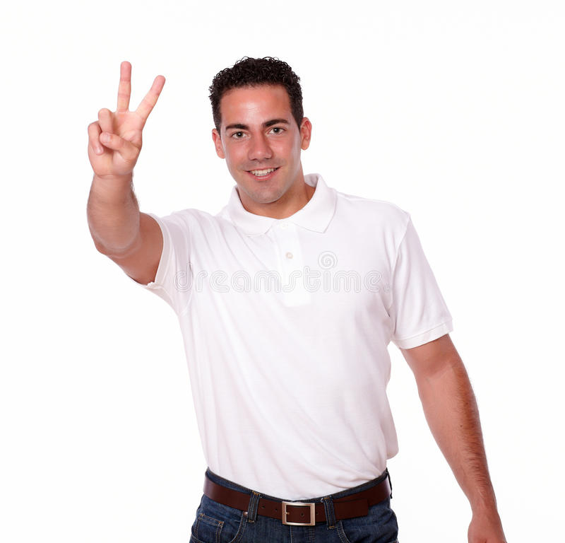 Gorgeous latin guy with winning sign. Portrait of a gorgeous latin guy on white t-shirt with winning sign smiling and looking at you on isolated background stock photo