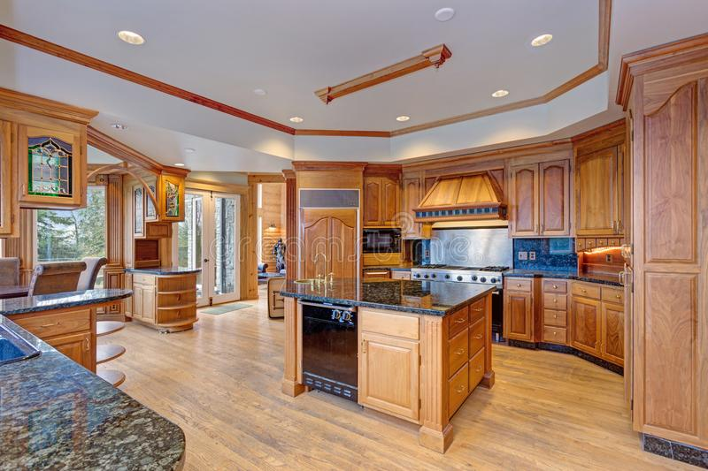 Gorgeous light filled mansion features an opulent kitchen. With rich wood cabinetry with marble countertops and an oversized kitchen island royalty free stock photo