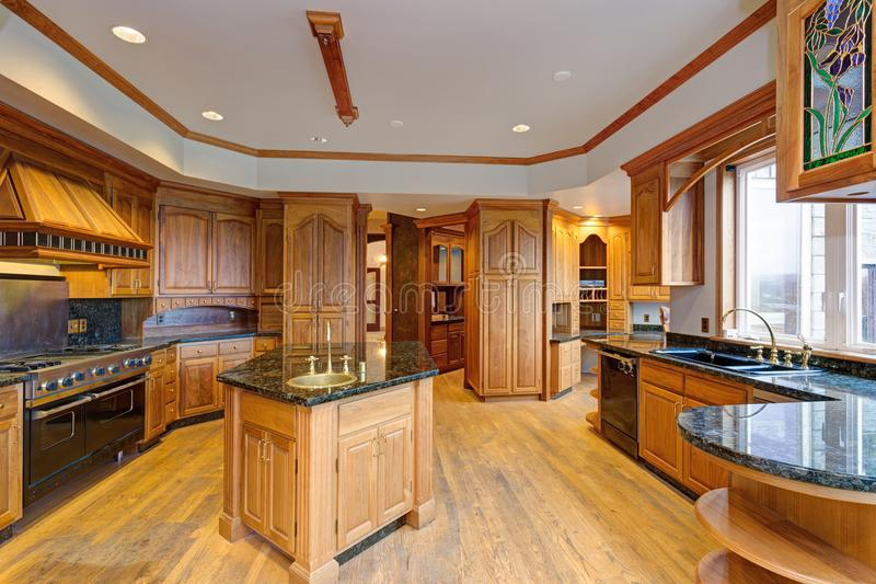Gorgeous light filled mansion features an opulent kitchen. With rich wood cabinetry with marble countertops and an oversized kitchen island royalty free stock image