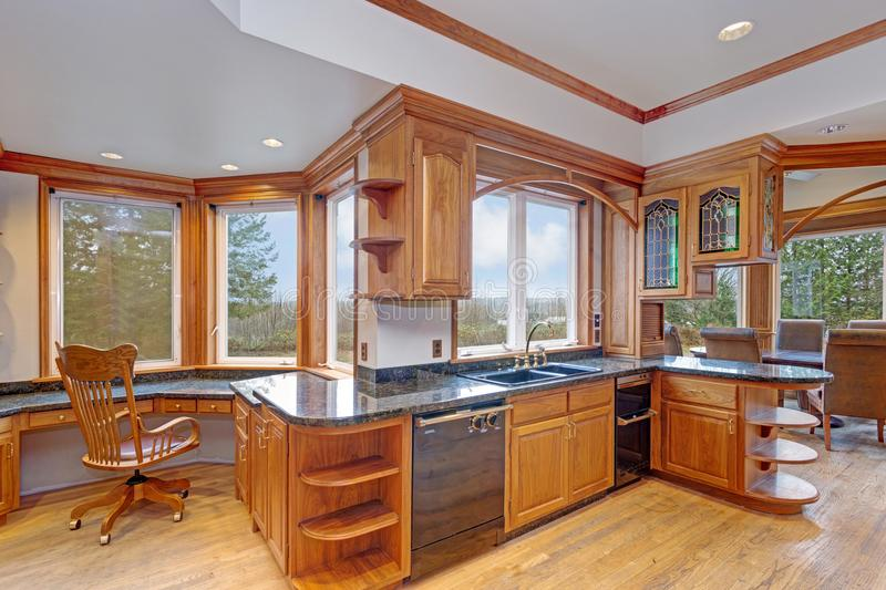 Gorgeous light filled mansion features an opulent kitchen. With rich wood cabinetry and marble countertops stock photo