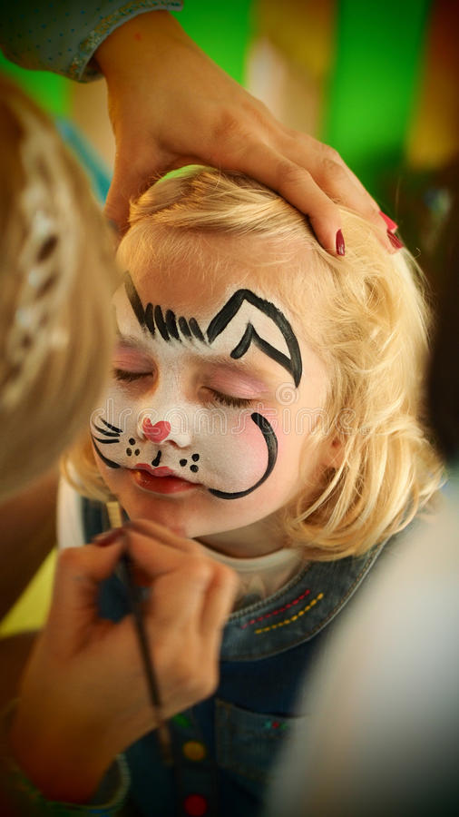 Gorgeous little girl rabbit face painting Easter. Blond blue eyed little girl face painting as rabbit for Easter party stock photo