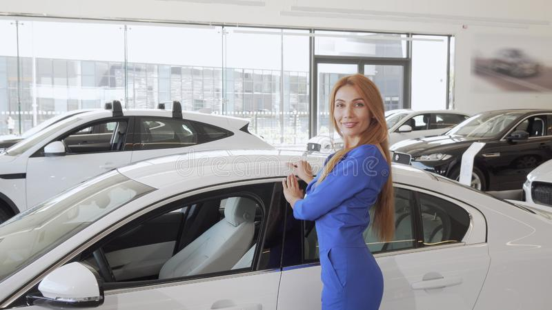 Gorgeous long haired woman stroking new expensive automobile at dealership stock images
