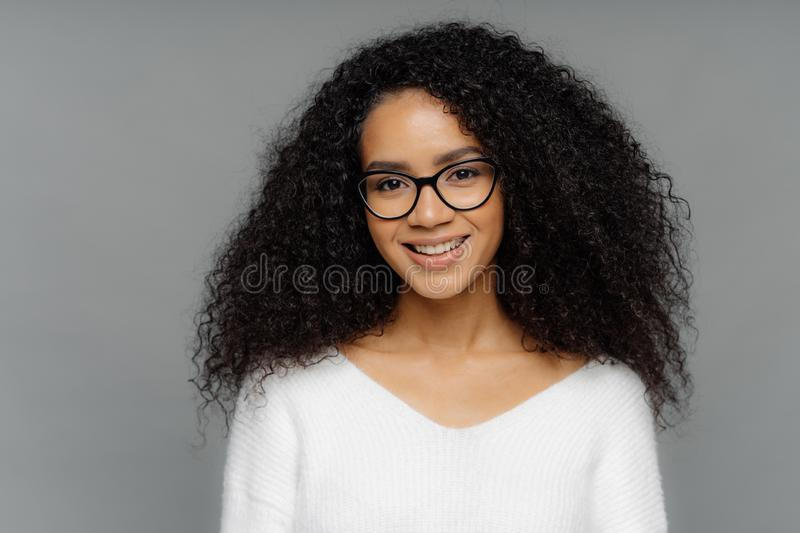Gorgeous lovely curly woman with Afro hairstyle, feels glad, smiles gently at camera, wears optical glasses and white sweater,. Isolated on grey background stock image