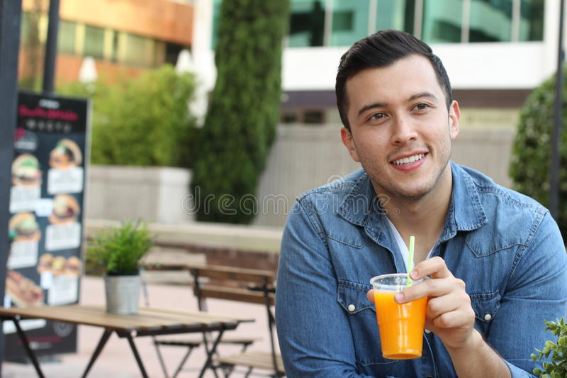 Gorgeous male cheering with a cold glass of orange juice looking away with copy space stock photos