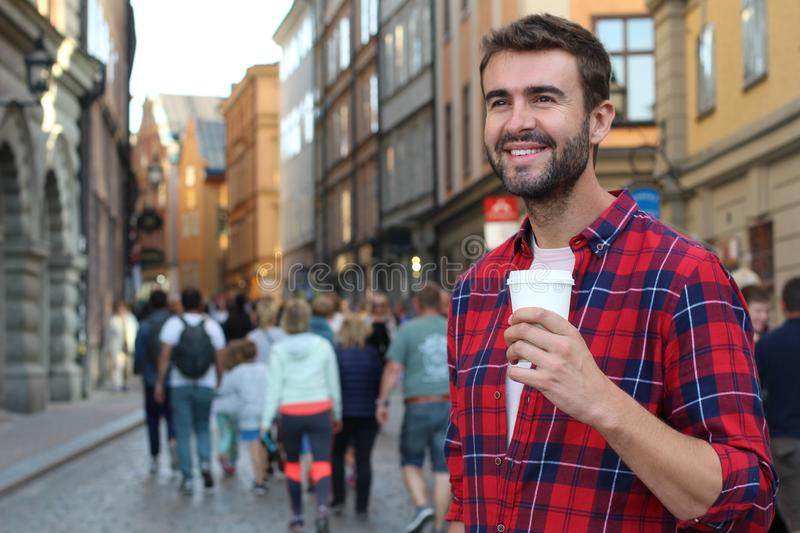 Gorgeous male holding a disposable cup of coffee in the a crowded city street.  royalty free stock photos