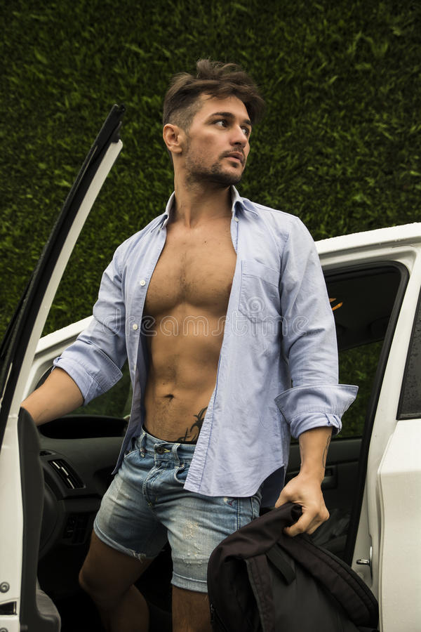 Gorgeous Man in Beach Attire Getting Out his Car. Gorgeous Young Man in Beach Attire Getting Out his Car, Showing Body Abs. Looking to His Left royalty free stock photo