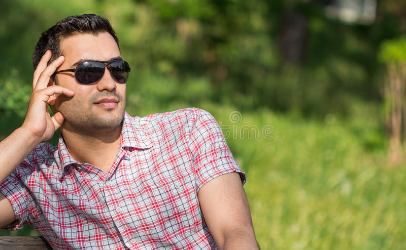 Gorgeous man. Close up handsome man. Profile - portrait of a attractive gorgeous guy with sunglasses, outdoor-park stock photography