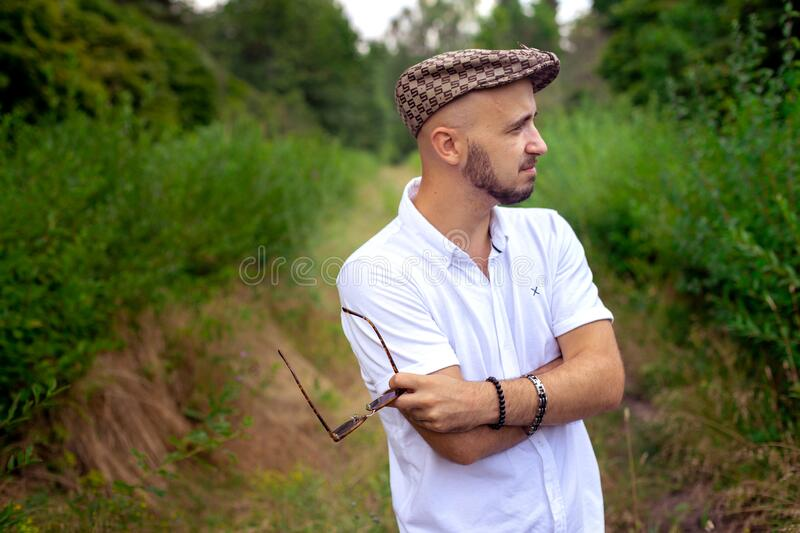 Gorgeous man in hat holds sunglasses and looking away at the green garden stock images