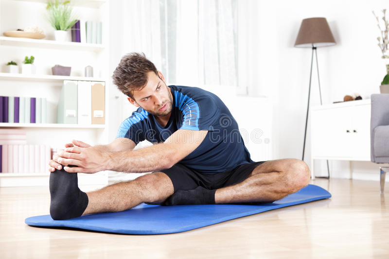 Gorgeous Man Performing Hamstring Stretch at Home royalty free stock photos