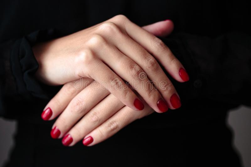 Gorgeous manicure, clssic red color nail polish, closeup photo. Female hands over dark background. Gorgeous manicure, clssic red color nail polish, closeup photo stock photos