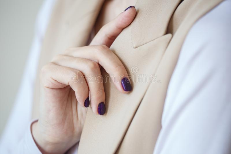 Gorgeous manicure, dark purple tender color nail polish, closeup photo. Female hands over simple background of casual clothes stock photography