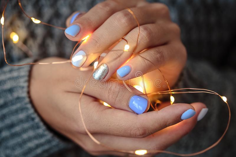 Gorgeous manicure, pastel tender color nail polish, closeup photo. Female hands hold a christmas light garland. Over grey knit background royalty free stock photography