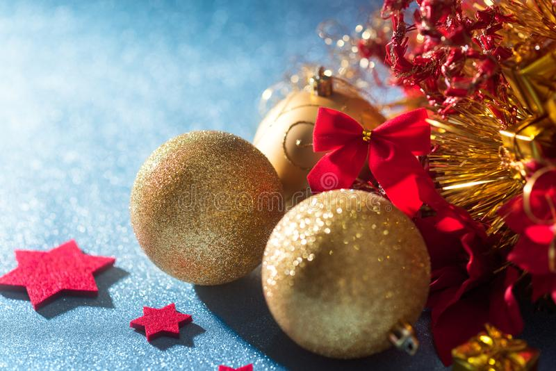 Gorgeous metallic gold christmas baubles, red stars and wrapped present on shiny blue background. Christmas border royalty free stock photo